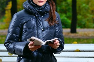 young woman is sitting on a bench in an autumn park and reading