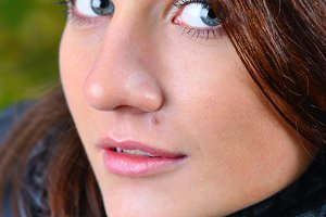 close up portrait of a beautiful young brown haired woman lookin