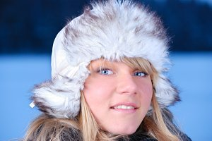 beautiful young woman in furry hat at winter evening