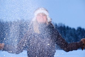 woman is throwing snow at winter evening