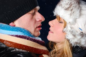 attractive young couple is kissing at winter evening