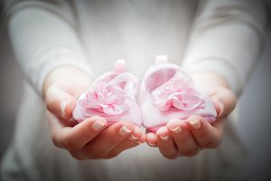 Little baby shoes in woman's hands.