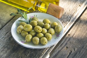 dish of olives on wooden background