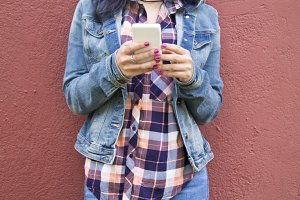 young woman with mobile phone on the wall