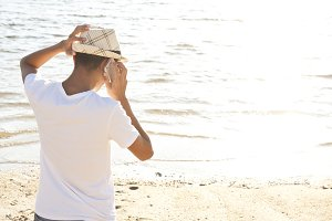 man calling by cell phone on the beach in summer