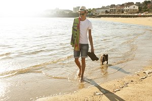 man walking with the dog on the beach. Summer evening, soft light