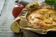 Apple pie on rustic wood background