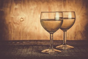 Glasses with white wine on rustic wood background