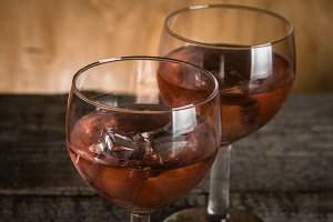 Glasses with rose wine on rustic wood background