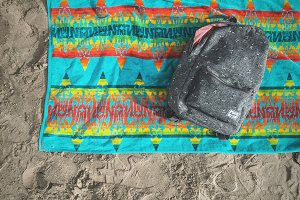 Backpack and Towel on the Beach
