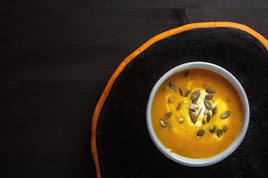 Fresh homemade carrot soup with pumpkin seeds and sour cream in a blue vintage plate. Dark wood background