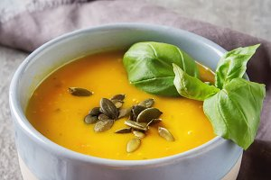 Fresh homemade carrot soup with pumpkin seeds and basil in a blue vintage plate. Grey stone background