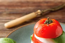 Fresh italian Caprese salad tomato and mozzarella slices with basil leaves on a blue plate with vintage yellow fork. Dark wooden background