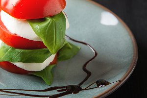 Fresh italian Caprese salad tomato and mozzarella slices with basil leaves balsamic vinegar on a blue plate. Dark wooden background