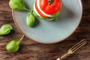 Fresh italian Caprese salad tomato and mozzarella slices with basil leaves on a blue plate with vintage yellow fork. Dark wooden background. Top view