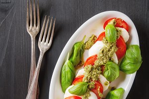 Fresh italian Caprese salad tomato and mozzarella slices with basil leaves green pesto on a blue plate. Dark wooden background. Top view