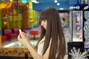 Young woman playing Pokemon GO indoor at shopping center, using smart phone. Girl play the popular smartphone game - catching pokemon in hypermarket mall