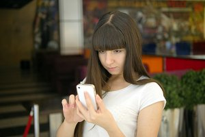 Young woman playing Pokemon GO indoor at cafe, using smart phone. Girl play the popular smartphone game - catching pokemon