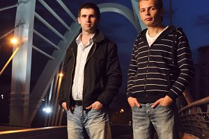 two guys standing on the night bridge and looking at camera