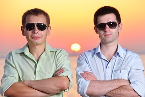 two friends at sunset wearing sunglasses fold their arms