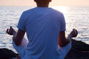 young man is sitting on a stone and looking at sea sunrise. view