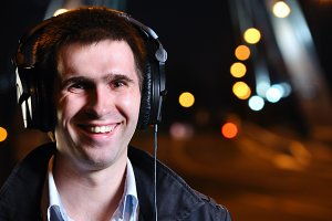 smiling man is listening music at city night street
