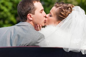 wedding couple is kissing