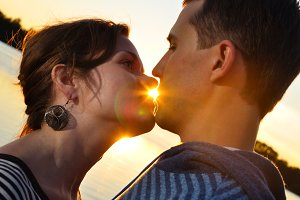 young attractive couple is kissing at sunset