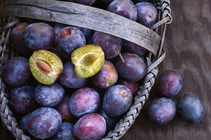 Fresh ripe black plums in a basket