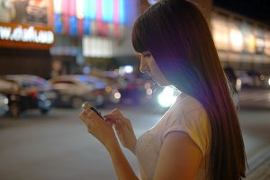 Young woman playing Pokemon GO outdoor at shopping center parking, using smart phone. Girl in evening play the popular smartphone game - catching pokemon
