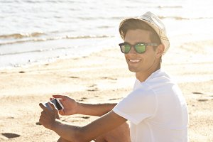 man on the beach smiling with mobile