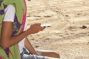 boy with the phone on the beach