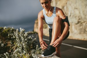 Female runner tying shoe laces