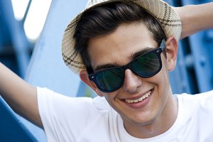 close-up portrait of young man with hat smiling