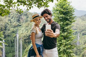Couple taking selfie with waterfall