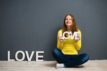 Beautiful young woman is holding a sign with the word: love
