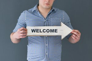 Young man holding welcome