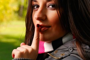 beautiful woman puts her finger to her lips
