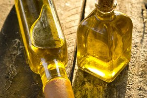 bottles of extra virgin olive oil on wooden background