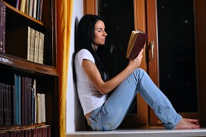 pretty woman is sitting on window and reading book