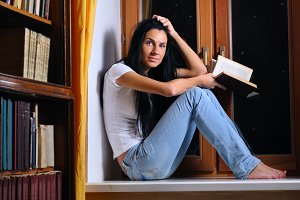 beautiful woman is sitting on a windowsill and holding a book