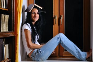 pretty woman is sitting on window with book on head