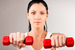 woman is holding barbells