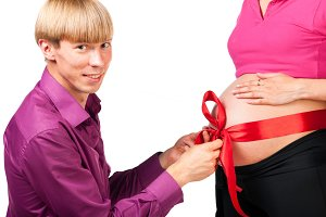 untying red silk bow on stomach of pregnant woman