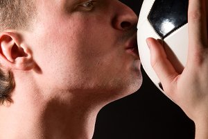soccer player is kissing the ball
