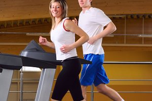 attractive couple is running on the treadmill