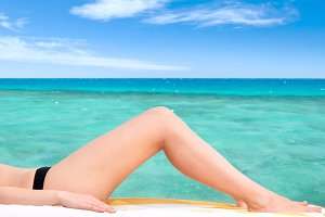 beautiful female legs against the sea background