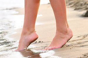 slim female legs steps to the sea