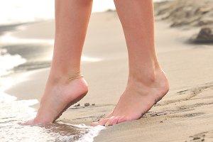 female legs on sunrise beach