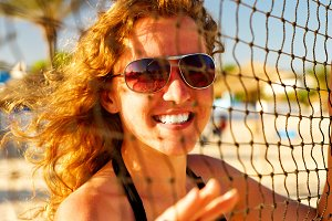 happy woman behind the volleyball net